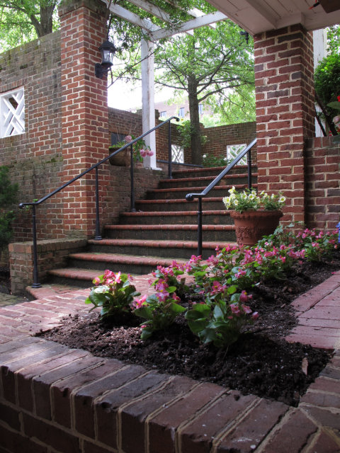 Flowers potted in a brick bench, surrounded by brick.  Also brick stairs and a trellis.