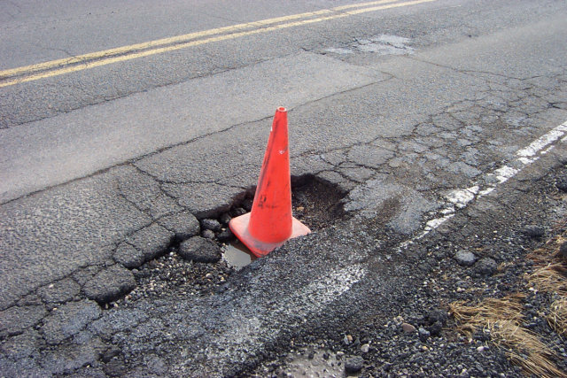An orange cone sticking out of a pothole.