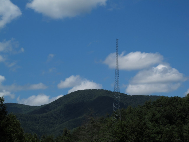 A radio tower with lots of greenery and hills and stuff.