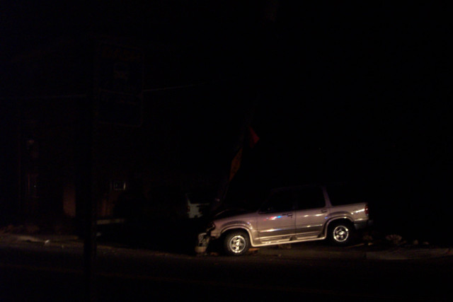 A low quality picture of an SUV crashed into a telephone pole.