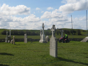 A guy mowing the lawn in a cemetary, at Clonmacnoise.